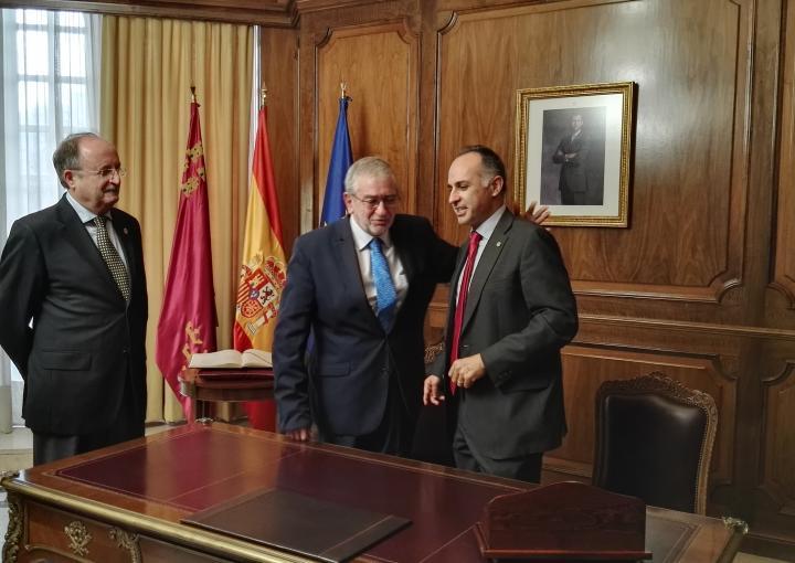 El presidente de la Asamblea, Alberto Castillo, y el rector de la UPCT, Alejandro Díaz Morcillo, se felicitan tras la firma del acuerdo, en presencia de Tomás Martínez Pagán
